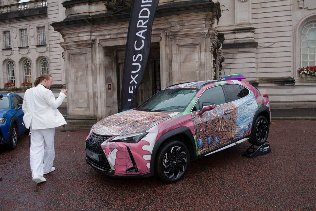 Artist Nathan Wyburn with his Cardiff-inspired artwork wrapped onto a Lexus UX hybrid SUV